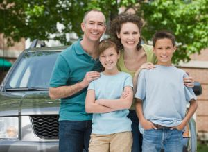Family with two children in front of car