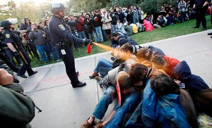 UC Davis Police Lt. John Pike uses a can of pepper spray to move protestors who were blocking officers attempts to remove arrested protestors from the Quad on Friday afternoon. Wayne Tilcock/Enterprise photo